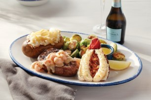During Ultimate Surf & Turf™, Red Lobster® guests can enjoy its NEW! Lobster and Seafood Topped Steak – a perfect pairing of steamed Maine lobster tail and a choice of wood-grilled top sirloin, filet or New York strip topped with creamy langostino lobster. (PRNewsfoto/Red Lobster Seafood Co.)