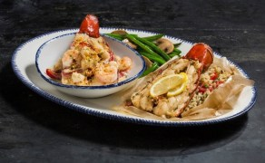 During Lobsterfest, Red Lobster® guests can enjoy its NEW! Dueling Lobster Tails™ – Maine lobster tail steamed in parchment paper with fresh herbs, tomatoes and lemon, paired with a grilled Maine lobster tail topped with shrimp, bay scallops and roasted bell peppers in a rich sherry lobster cream. (PRNewsfoto/Red Lobster Seafood Co.)