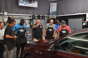 Justin Labato (center) shows certification class how to see and remove fine scratches on a vehicle (PRNewsfoto/Justin Labato)