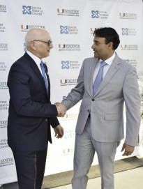 Dr. Stephen D. Nimer (left), director of the Sylvester Comprehensive Cancer Center, and Dr. Amit Rastogi, president and CEO of Jupiter Medical Center, shake hands to celebrate the affiliation agreement between the two organizations.